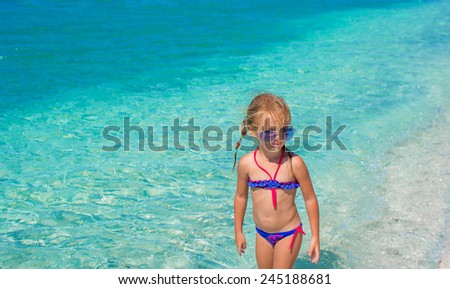 Little girl having fun on tropical beach with turquoise ocean water - stock photo