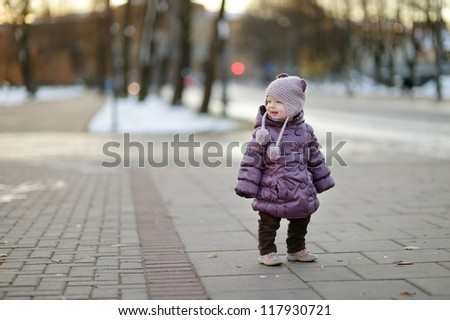 Little girl having fun on winter day in city - stock photo