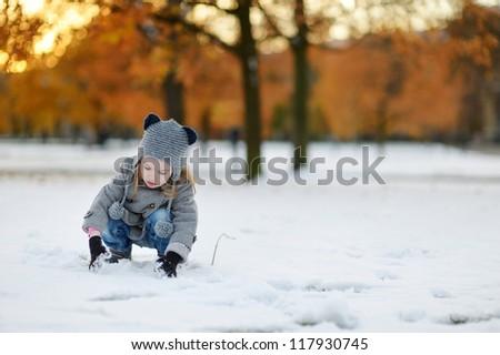 Little girl having fun on winter day in city - stock photo