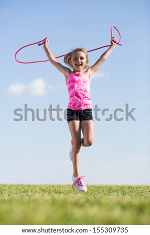 Little girl having fun outdoors with a skipping rope - stock photo