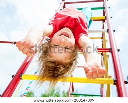 Little girl having fun playing on monkey bars - stock photo