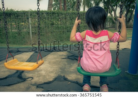 Little girl having fun  playing swing at the park - stock photo