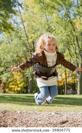 Little Girl Having Fun Swinging - stock photo
