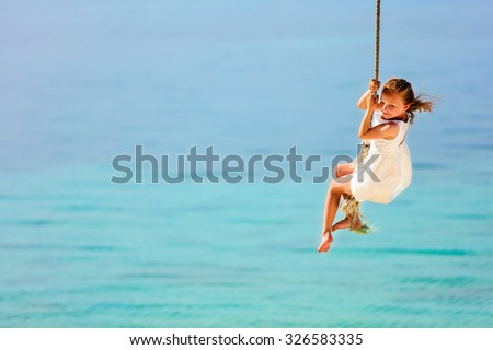 Little girl having fun swinging on a rope at tropical island beach - stock photo