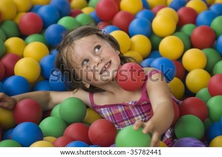 Little girl having fun time in balls pool - stock photo