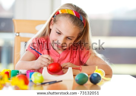 little girl having fun to paint easter eggs - stock photo
