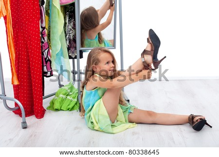 Little girl having fun trying her mother's shoes and clothes - stock photo