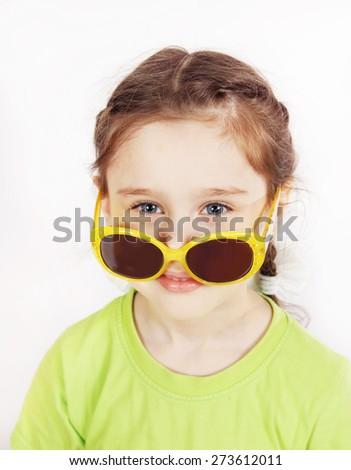 Little girl having fun wearing sunglasses on her nose - stock photo