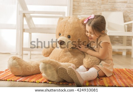 Little girl having fun with plush bear toy. Playing with teddy bear at home. Childhood happiness concept. Portrait of expressive charming little girl hugging huge plush bear, laughing. - stock photo