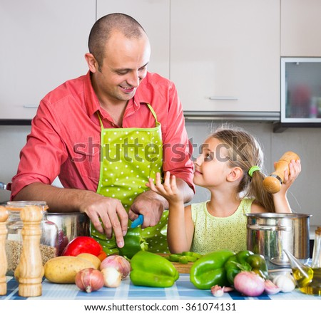 Little girl helping father to prepare dinner in kitchen - stock photo