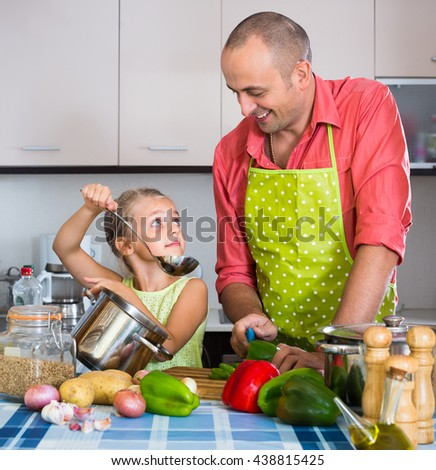 Little girl helping father to prepare salad  indoors - stock photo