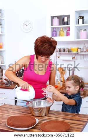 Little girl helping her mom making the cake