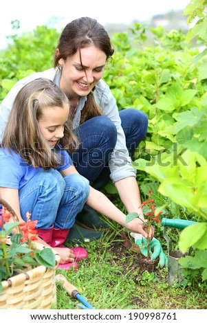 Little girl helping her mother to do gardening