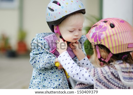 Little girl helping her sister to put a bicycle helmet - stock photo