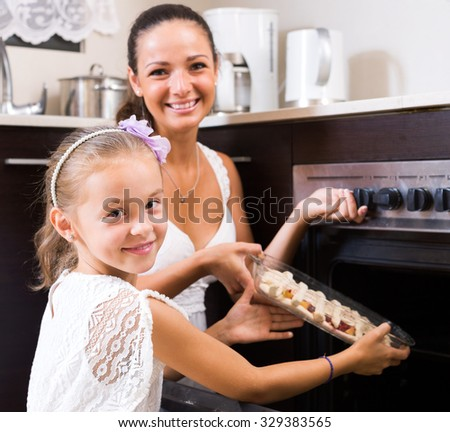 Little girl helping mom to make apple cake at home. Focus on the girl