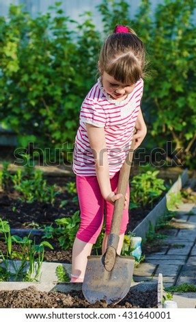 little girl helps parents, digs up the flower bed with a shovel in summer day - stock photo