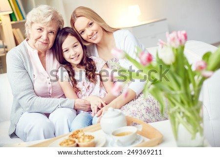Little girl, her mother and grandmother sitting on sofa together - stock photo
