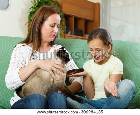 Little girl, her mother and Siamese cat on sofe at home - stock photo