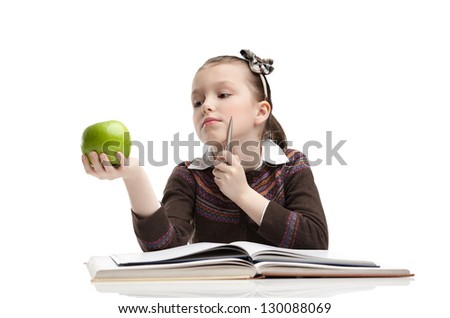 Little girl hesitates about eating a ripe green apple, isolated, white background - stock photo