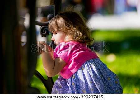 Little girl hiding behind a bench in the park. Summer  - stock photo
