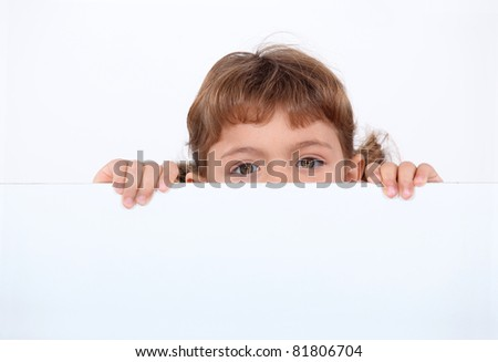 little girl hiding behind a board
