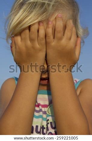 little girl hiding behind her hands - stock photo