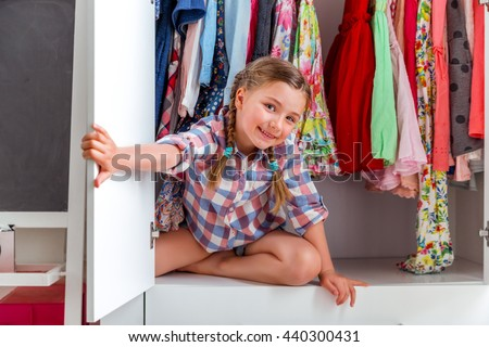 little girl hiding herself in furniture