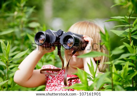 Little girl hiding in grass looking through binoculars outdoor - stock photo