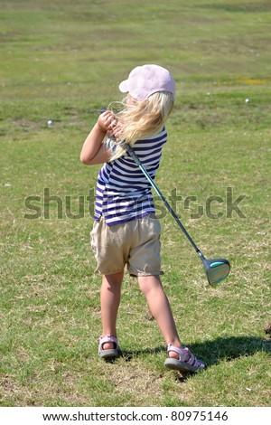 little girl hitting golf balls - stock photo