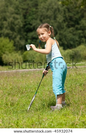 Little girl holding a badminton racket and shuttlecock - stock photo