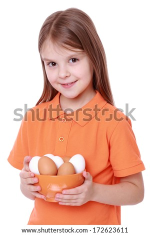Little girl holding a bowl of eggs. - stock photo