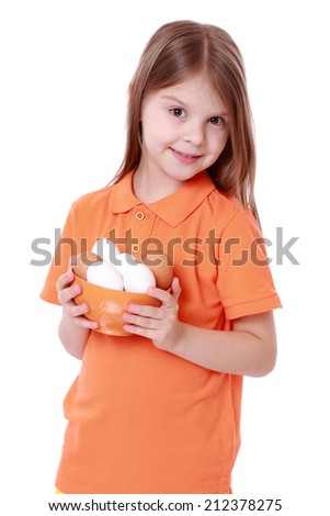 Little girl holding a bowl of eggs isolated over white - stock photo