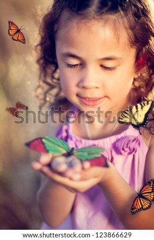 Little girl holding a butterfly in a field - stock photo
