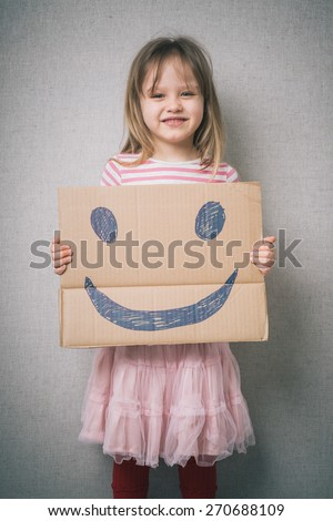little girl holding a cheerful face - stock photo