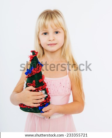 Little girl holding a Christmas tree