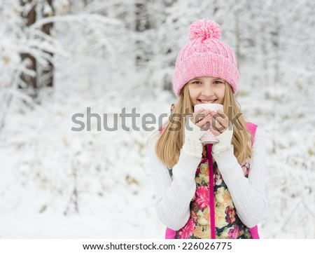 little girl holding a cup of hot drink and smiling at the background of a winter forest - stock photo
