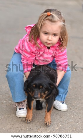 Little girl holding a dog in her arms - stock photo