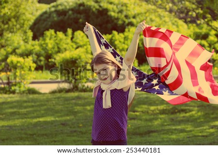 little girl holding a large American flag. Image with instagram filter.