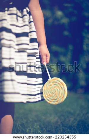 Little girl holding a lollipop in her hand. Closeup. - stock photo