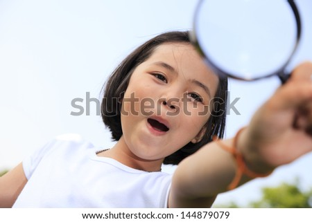 Little girl holding a magnifying glass - stock photo