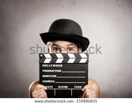 little girl holding a movie clapper board on a grey background - stock photo