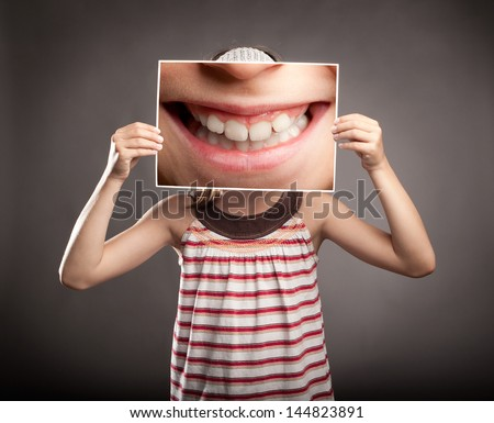 little girl holding a picture of a mouth smiling - stock photo