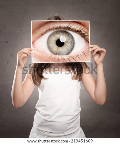 little girl holding a picture of an eye watching - stock photo