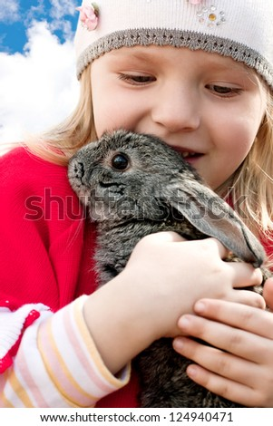 little girl holding a rabbit in her arms
