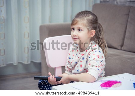 Little girl holding a remote control and watching tv.