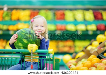 Little girl holding a ripe watermelon while sitting in a shopping cart in a food store or a supermarket