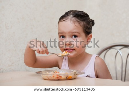 Little girl holding a spoon with food and eating