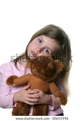 Little girl holding a teddy bear isolated on white and looking into camera with pensive expression - stock photo