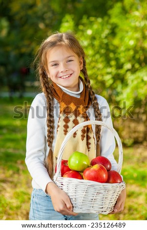Little girl holding a white basket with red and green apples. Autumn harvest.