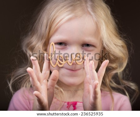 little girl holding a word Love at her hands  - stock photo